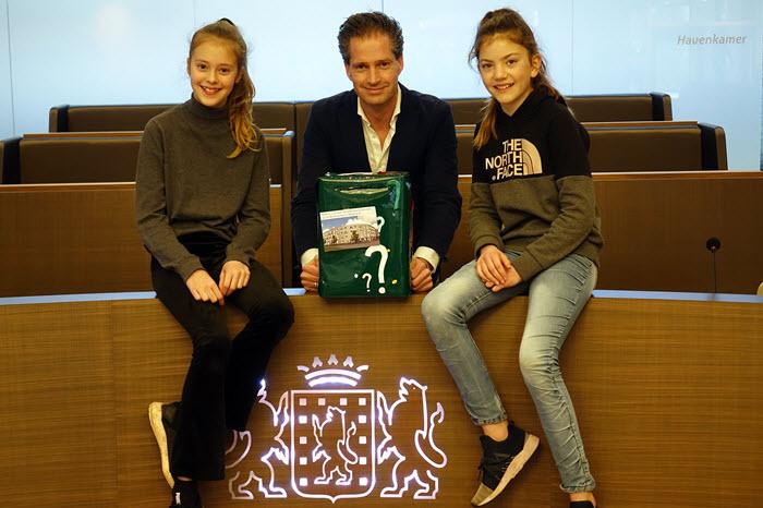 Wethouder Jeroen de Jong nam de reizende box over van Anna (links) en Lauren (rechts) van Daltonschool de Veste