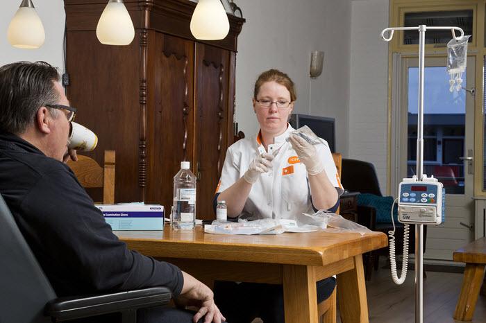 Een oncologie verpleegkundige van Icare geeft een patiënt thuis immuuntherapie.